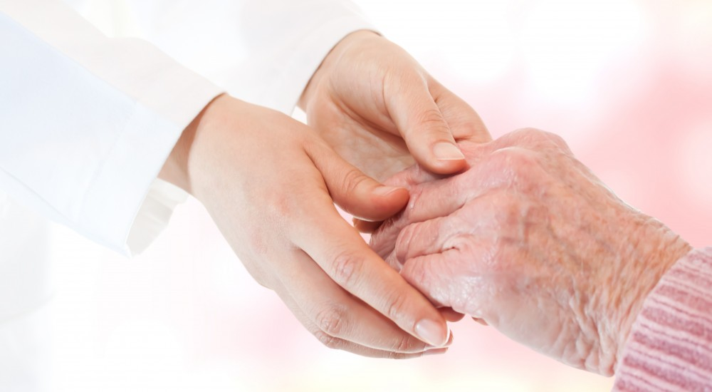 Doctor holding senior lady's hand